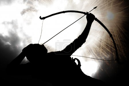 Photo for A silhouette of an archer, on the backdrop of a sky with exploding gun powder. - Royalty Free Image