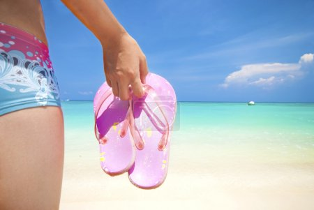 Photo for Asian girl on a beach holding slipper with copyspace on right - Royalty Free Image