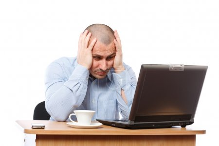 Photo for Tired and stressed young businessman working at his computer - Royalty Free Image