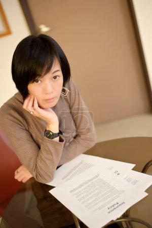 Photo pour Femme asiatique livre de police d'assurance sur le bureau dans le Bureau - image libre de droit