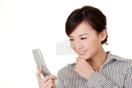Foto de Mujer de negocios sonriente buscando mensaje en el teléfono celular, retrato de primer plano en blanco . - Imagen libre de derechos