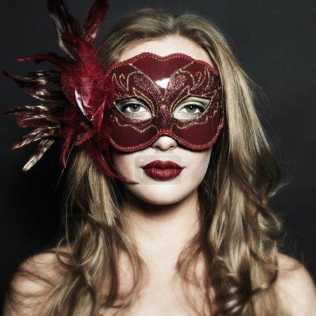 Photo pour Belle jeune femme dans un masque vénitien mystérieux rouge - image libre de droit