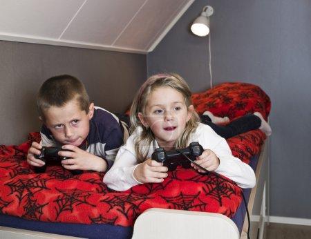 Photo pour Frères et sœurs jouant à des jeux vidéo dans le lit - image libre de droit