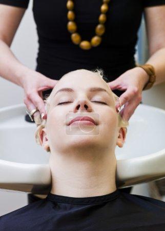 Photo pour Coiffeur lavant les cheveux des clients dans un Beauty Spa - image libre de droit