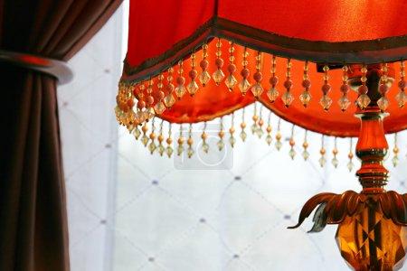 Orange lamp against drapes
