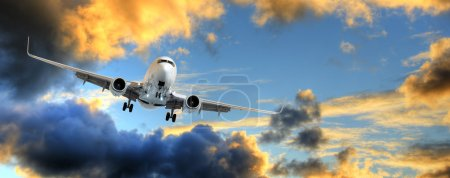 Photo for Flying away: panorama of airplane taking off in dramatic sunset sky with copy space. - Royalty Free Image