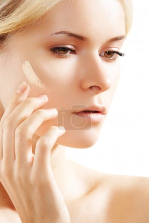 Cosmetology & cosmetic. Woman applying face skin foundation