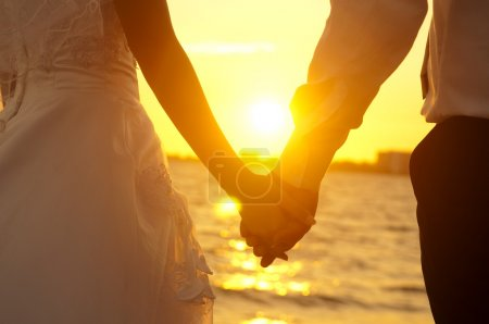 Photo for Young adult male groom and female bride holding hands on beach at sunset. - Royalty Free Image