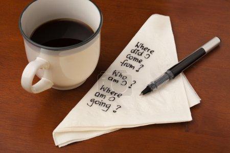 Photo pour Qui suis j'et autres questions de la vie spirituelle - écriture sur serviette avec une tasse de café sur la table en bois - image libre de droit