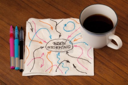 Photo pour Concept de remue-méninges - flèches représentant des idées, des entrées et des commentaires croquis sur une serviette avec une tasse de café sur la table - image libre de droit