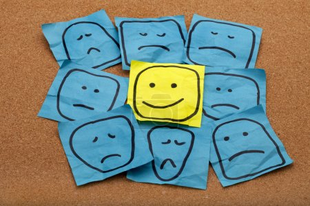 Photo for Positive attitude or optimism concept - happy smiley face on yellow sticky note surrounded by sad unhappy blue faces - Royalty Free Image