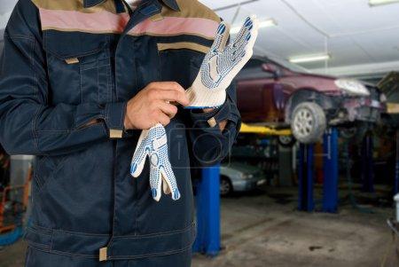 Auto mechanics closeup standing in his workshop...