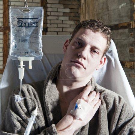 Photo pour Homme très malade, avec un égouttement d'iv assis sur une chaise - image libre de droit