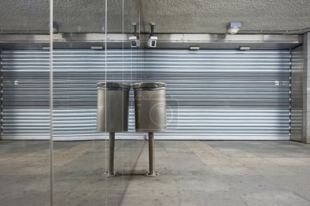 Photo pour Poubelle et volets avant fermés le long d'un mur miroir dans une station de métro déserte - image libre de droit