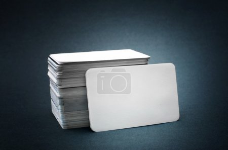 Photo pour The pile of blank business cards lays propped up another business card. - image libre de droit