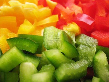 Foto de Amarillo, rojo y verde pimientos búlgaro. rebanar. cubos - Imagen libre de derechos