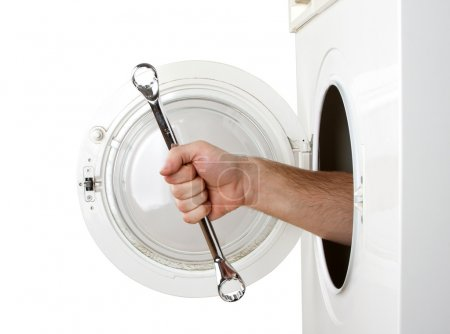 Photo for Repairman servicing washing machine. Isolated on white - Royalty Free Image