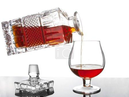 Photo pour Verser le cognac de la bouteille dans un verre - image libre de droit