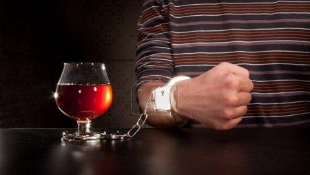 Photo pour Verrouillé à la main au verre d'alcool par des menottes - image libre de droit