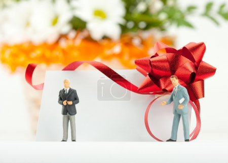 Figurines of businessmen with gift card