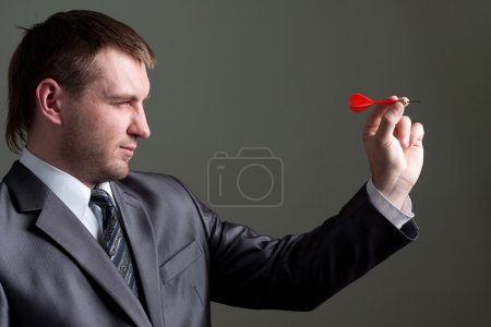 Photo for Business games - young businessman aiming by dart - Royalty Free Image