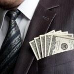 Formal weared businessman with earned money in sui...