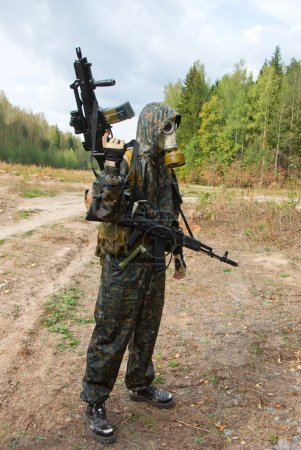 Photo pour Un soldat porte seul un gilet pare-balles, un camouflage et un masque à gaz à la fine pointe de la technologie, tenant une arme automatique . - image libre de droit
