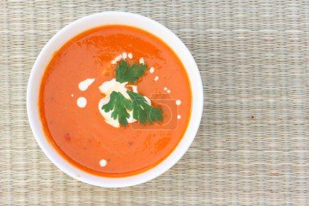 Foto de Arriba abajo vista de sopa de tomate rojo en un tazón blanco salpicado de crema - Imagen libre de derechos