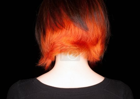 Photo for A young woman with a funky hair cut and color of orange and dark brown on a black background. - Royalty Free Image