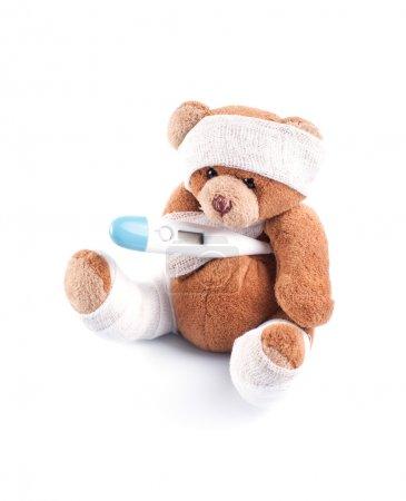 Photo pour Nounours malade enveloppé dans des bandelettes avec thermomètre aisselle, isolé sur fond blanc - image libre de droit