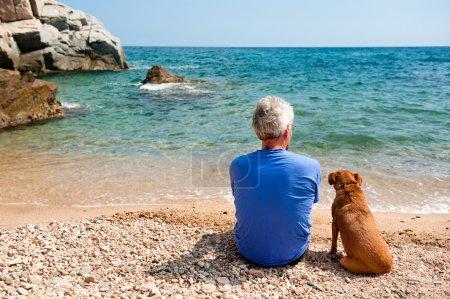 Photo pour Vieil homme avec son chien sur la plage l'été - image libre de droit
