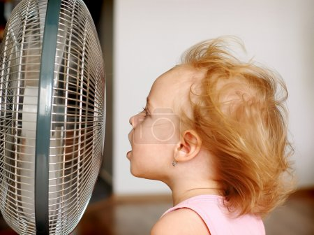 Photo for A little girl standing in front of fan - Royalty Free Image