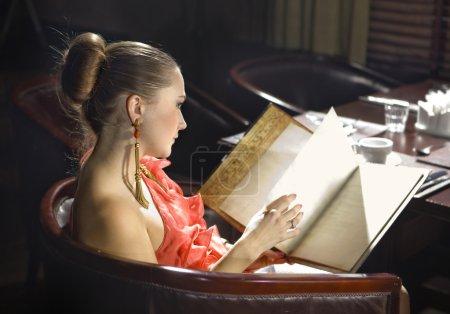 Photo pour Belle femme regarde dans menu au restaurant cher - image libre de droit