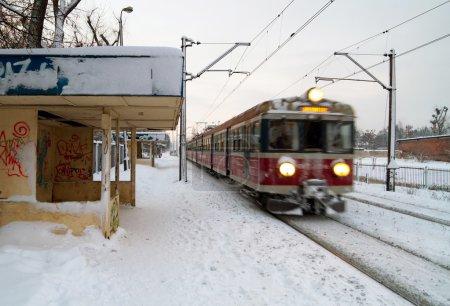 Photo pour Gare ferroviaire polonais à l'hiver avec le train en mouvement - image libre de droit