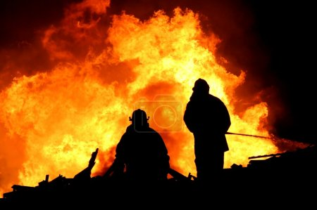 Two silhouetted firemen fighting a large fire...
