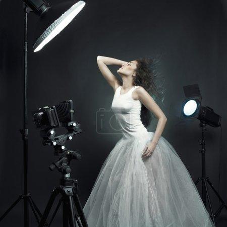 Photo pour Belle jeune femme en robe blanche pose en photo-studio - image libre de droit