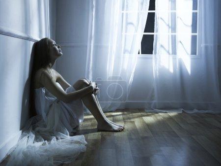 Foto de Retrato de joven hermosa en el interior de la ventana - Imagen libre de derechos