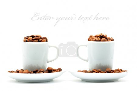 Two cups on plates filled with coffee beans