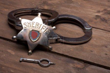 Photo pour Menottes et ancien insigne de shérif - image libre de droit