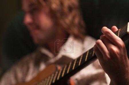 Photo pour Un jeune musicien joue de sa guitare acoustique sous un éclairage dramatique . - image libre de droit