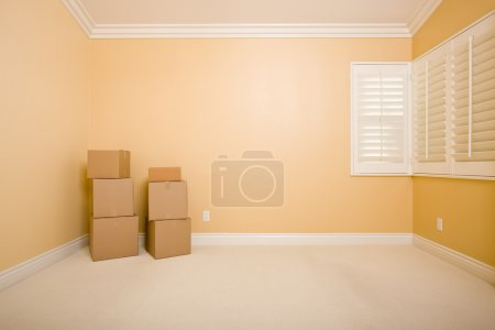Photo for Moving Boxes in Empty Room with Copy Space on Blank Wall. - Royalty Free Image