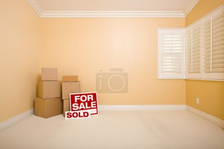 Boxes, Sale and Sold Real Estate Signs in Empty Room