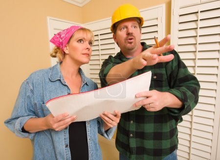 Contractor in Hardhat Discussing Plans with Woman
