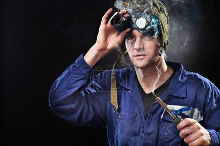 Photo pour Crazy génie gars portant chapeau bizarre avec fer à souder à la main - image libre de droit