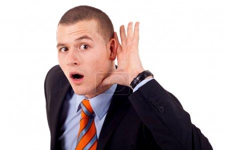 Photo pour Entreprise jeune homme ventouses main derrière l'oreille sur fond blanc - vous ne pouvez pas entendre concept - image libre de droit