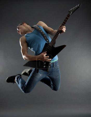Photo pour Guitariste passionné saute en l'air noir - image libre de droit