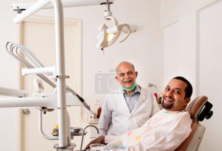 Photo pour Un senior dentiste indienne / asiatique et le patient les deux souriant à la caméra - il s'est bien passé! - image libre de droit