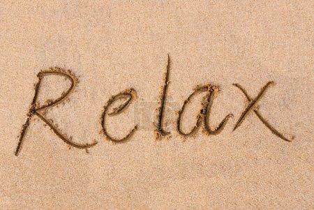 Photo pour Le mot relax écrite sur une plage de sable - image libre de droit