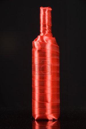 Photo pour Une bouteille de vin enveloppé dans du ruban rouge sur fond noir - image libre de droit
