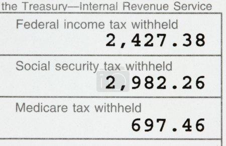 Photo pour Macro d'un w-2 montrant les impôts fédéraux, de sécurité sociale et d'assurance-maladie payés . - image libre de droit